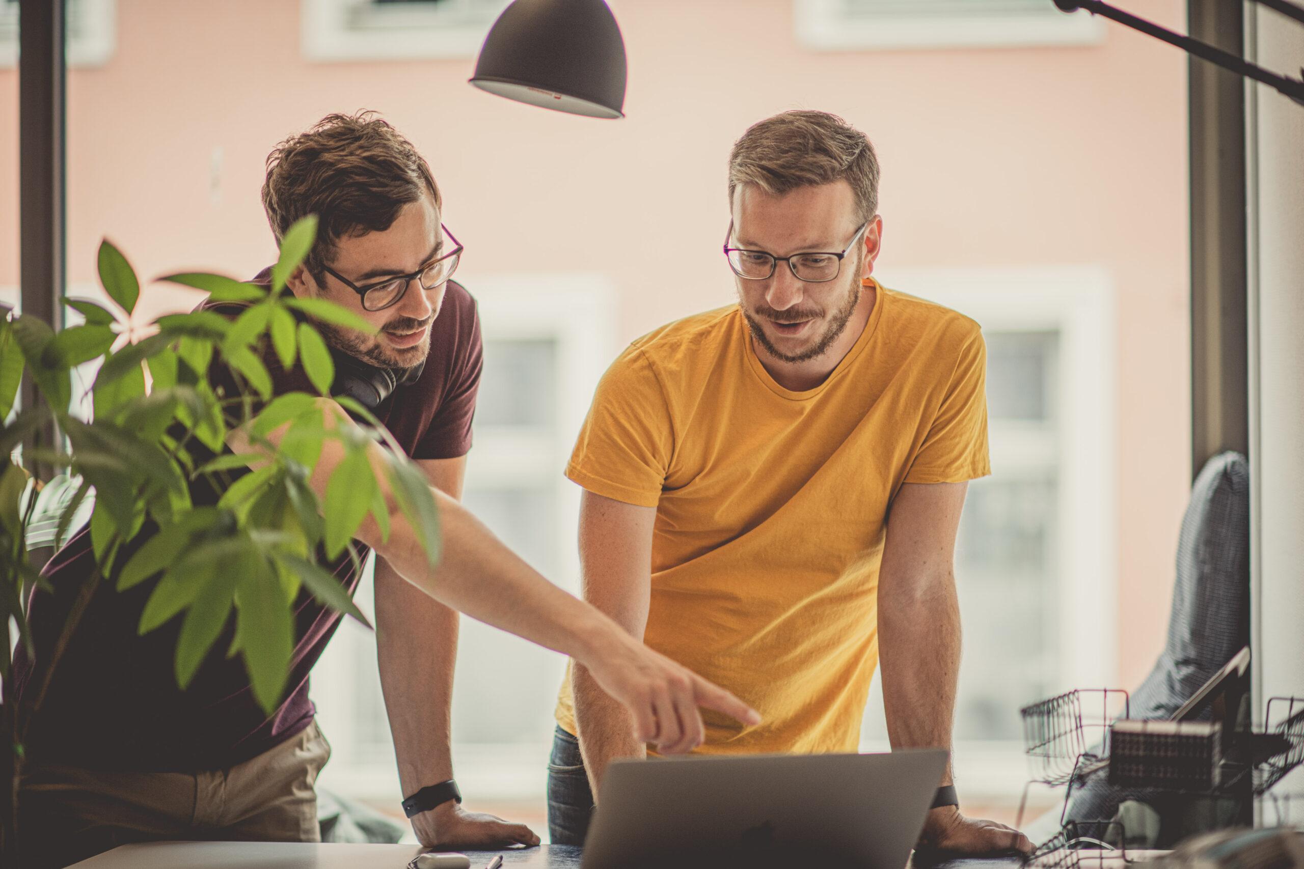 Två personer vid en laptop som samarbetar kring fastighetsunderhåll