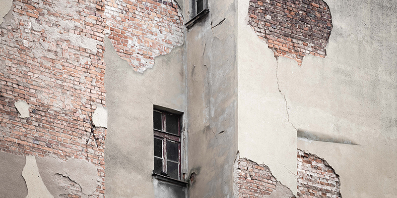 Skadad fasad på byggnad som därmed har en hög underhållsskuld.