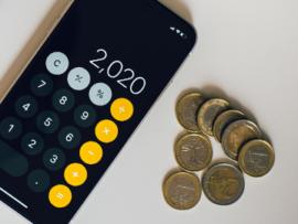 Mobiltelefon med kalkylator-app bredvid några mynt på en vit bordsskiva
