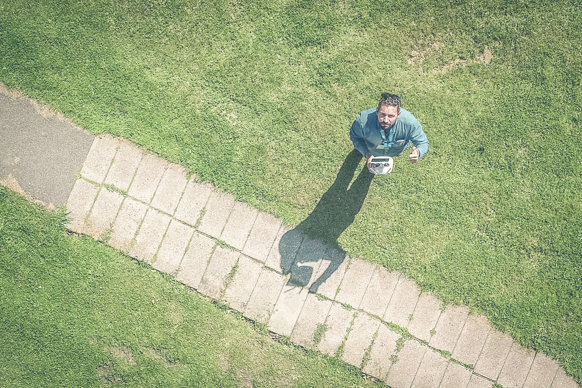 Konsult från Sustend stående på mark och tittar upp mot flygande drönare.