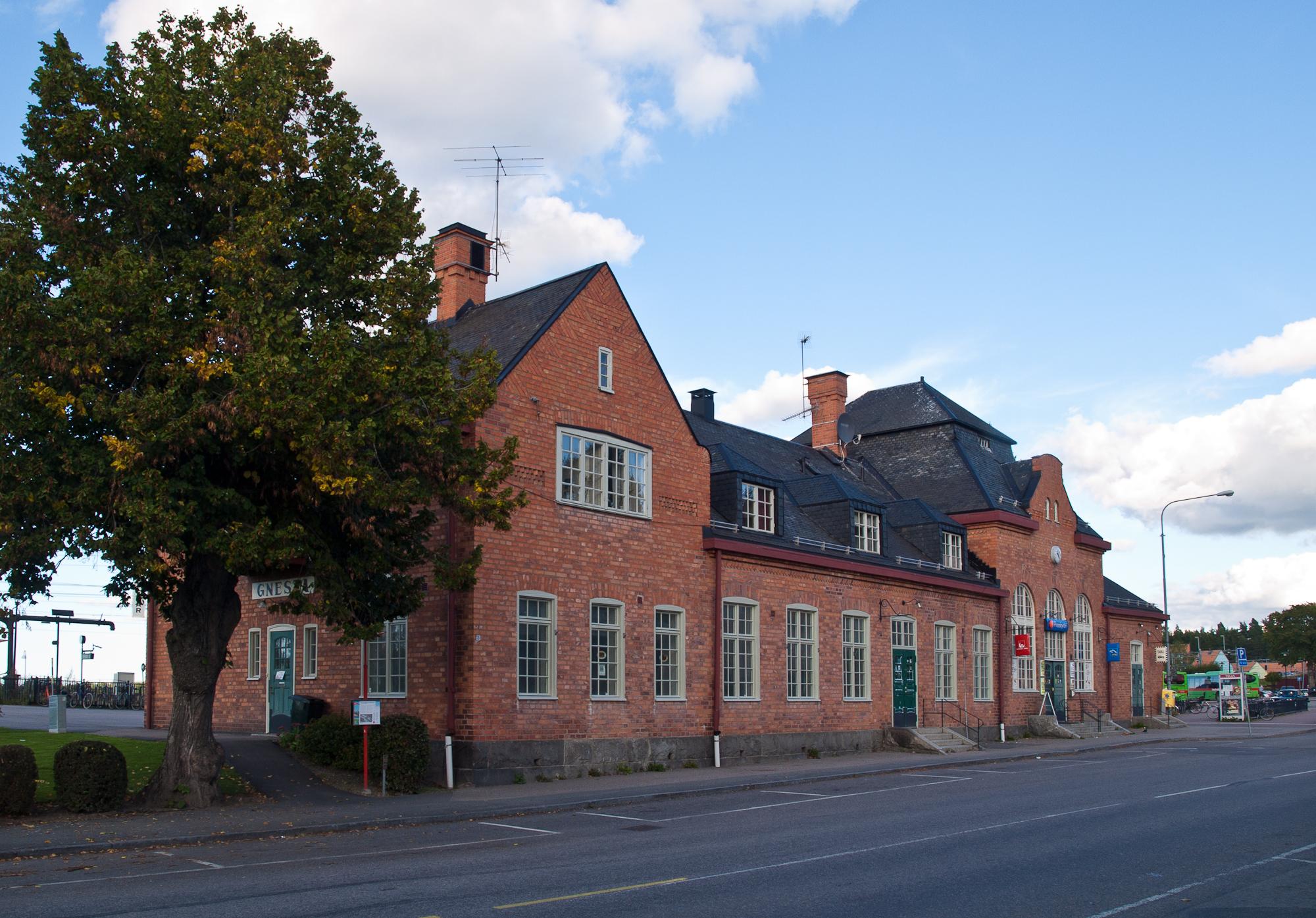 Gnesta tågstation, röd tegelbyggnad med asfaltsväg framför.