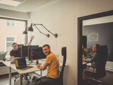 Planimas kontor och tre kollegor i teamet vid sina skrivbord