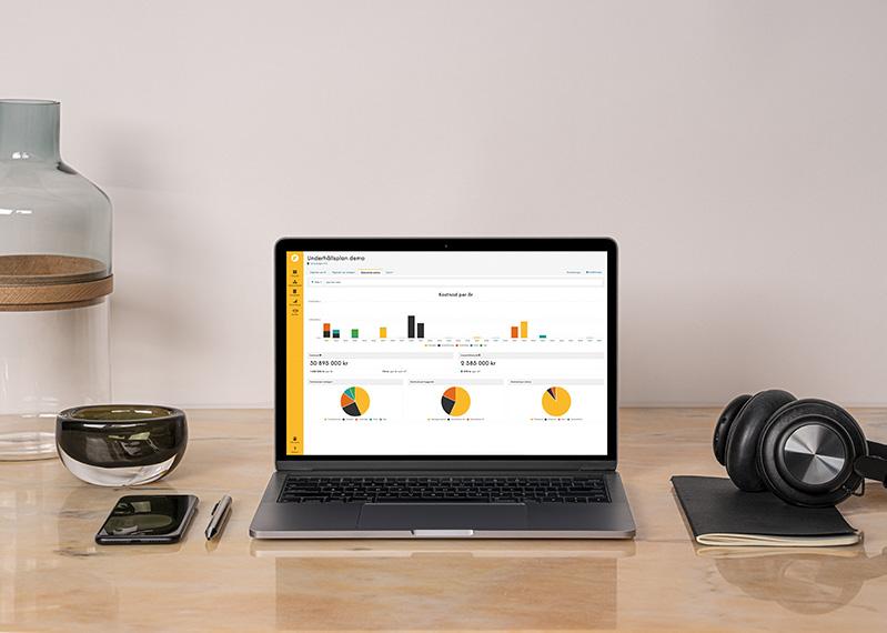 Laptop på skrivbord med underhållsplan i Planima på skärmen.